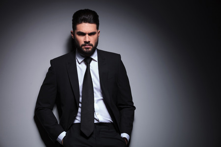 frown: portrait of a young fashion man leaning with his back on the wall while looking with anger at the camera and holding both hands in his pockets. on a dark background
