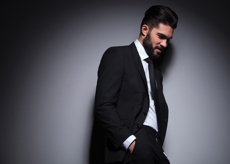 dark side: side view portrait of a young fashion man standing with his hands in his pockets while looking down, away from the camera, leaning on the wall. on a dark background