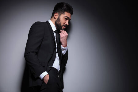 side view picture of a young fashion man leaning with his shoulder on a wall and looking away from the camera while holding a hand in his pocket and one on his chin. on a dark background photo