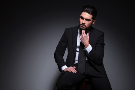 portrait of a pensive young fashion man sitting on a chair and looking away while holding his hand at his chin. on a dark background