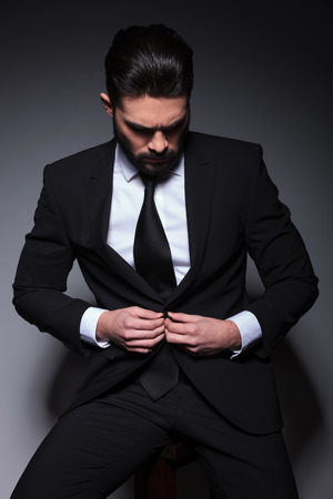 young business man sitting on a chair and buttoning his suit jacket while looking down, away from the camera. on a dark background photo
