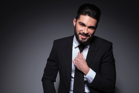 closeup photo of a young fashion man smiling for the camera while adjusting his tie. on a dark background
