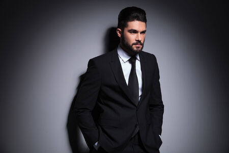 young fashion business man looking away from the camera while holding his hands in pockets. on a dark background photo