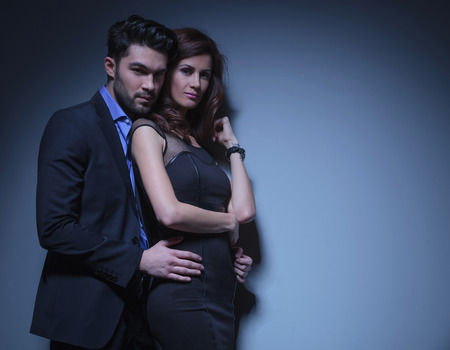 portrait of a young fashion couple looking into the camera while the man is holding the woman by her hips, from behind. on a dark blue background