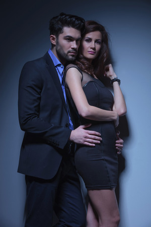 portrait of a young fashion couple where the man holds the woman from behind and looks away over her shoulder and she is looking into the camera. on a dark blue background photo