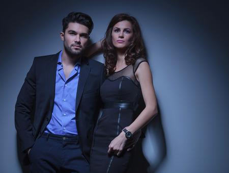 pareja apasionada: retrato de una joven pareja de moda que mira lejos de la c�mara, mientras que el hombre tiene la mujer y una mano en el bolsillo. sobre un fondo azul oscuro Foto de archivo