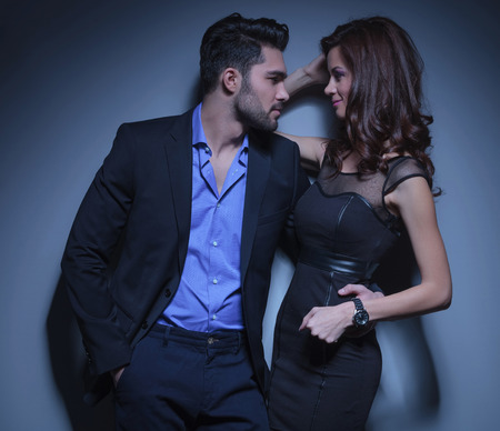portrait of a young fashion woman being held by a handsome man while they are looking into each other's eyes. on a dark blue background photo