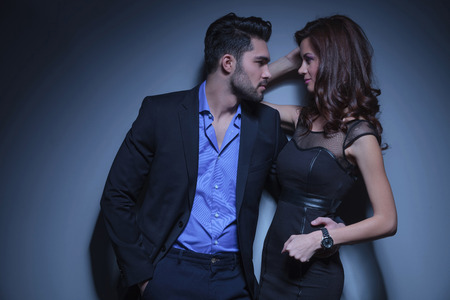 portrait of a young fashion couple looking at each other while the man holds a hand in his pocket and the other on the womans back. on a dark blue background