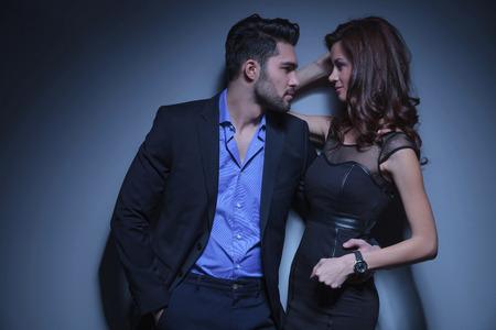 coquetear: retrato de una joven pareja de moda mirando el uno al otro, mientras que el hombre tiene una mano en el bolsillo y la otra en la espalda de la mujer. sobre un fondo azul oscuro