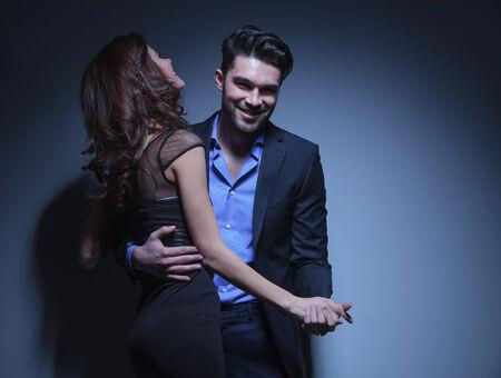 pareja bailando: retrato de una joven pareja de baile de moda, mientras que el hombre sonríe para la cámara y la mujer se ríe de distancia. sobre un fondo azul oscuro