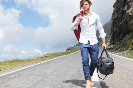 road shoulder: sexy young fashion man walking down the middle of a road in the mountains while holding his jacket over his shoulder and a bag in his hand and looking away from the camera  Stock Photo