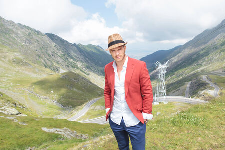portrait of a young fashion man posing outdoor, with his hands in his pockets while looking into the camera, over a breathtaking landscape of the Transfagarasan road photo