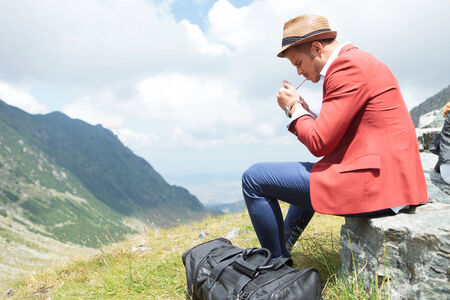 outdoor lighting: picture of a young fashion man lighting up a cigarette outdoor, in the mountains while sitting on a rock, with a breathtaking landscape behind him