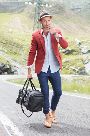 picture of a young fashion man walking on the middle of the road while holding a bag in his hand and smoking Stock Photo - 26380457