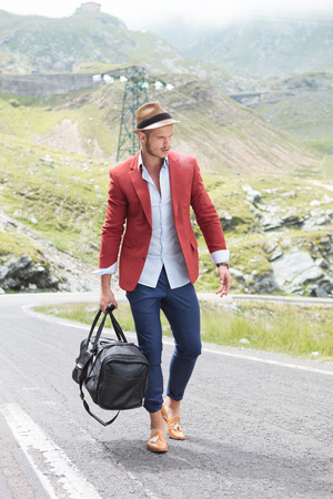 picture of a young fashion man walking on the middle of the road in the mountains while holding a bag in his hand and looking down, away from the camera photo