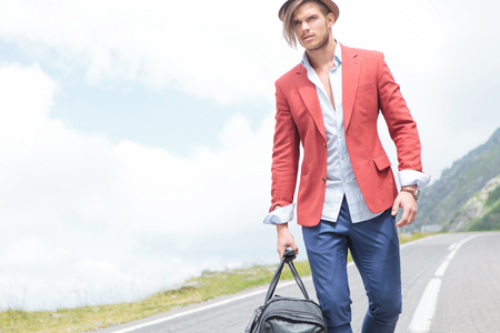 picture of a young fashion man carrying a voyage bag outdoor, while looking away from the camera photo