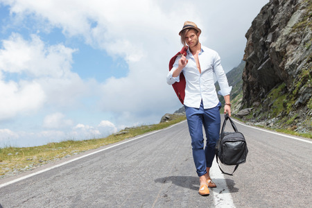 road shoulder: young fashion man walking down the road in the mountains, with his jacket over his shoulder and a bag in his hand, while looking into the camera