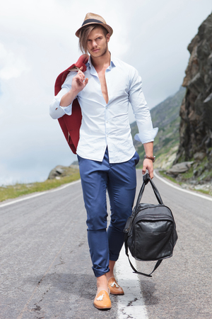 road shoulder: full length photo of a young fashion man walking down the middle of the road while holding his jacket over his shoulder and a bag in his hand