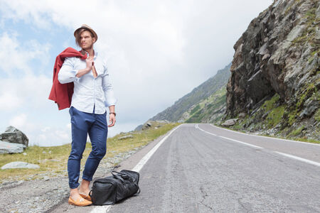 attractive young fashion man posing outdoor, on the side of the road, with his jacket over his shoulder and his bag at his feet, while looking away photo