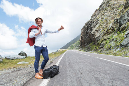 portrait of a young fashion man hitchhiking in the mountains with a smile on his face photo