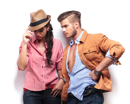 young casual man looking at his girlfriend, she is holding her hat and looks down photo
