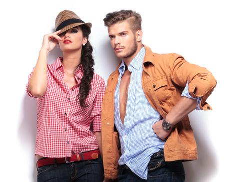 時尚: 年輕休閒時尚機型擺在工作室,女人看在camaera和男子望著遠處他的身邊