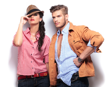 casual fashion: young casual fashion models posing in studio, woman looking at the camaera and man looking away to his side Stock Photo