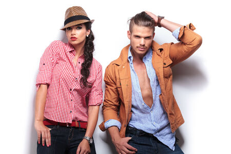 casual fashion: young casual fashion man passing his hand through  his hair while his girlfriend poses with hands in pockets