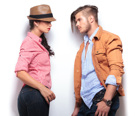 other side of: side view of a young casual couple in jeans looking at each other  Stock Photo