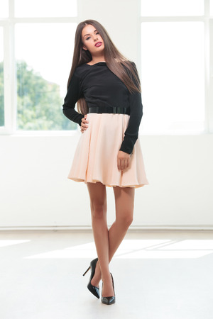full length portrait of a young fashion woman posing with her hand on her hip and her legs crossed while looking into the camera, in a studio with natural light photo
