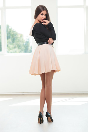 full length picture of a young fashion woman standing with her back at the camera while looking at you over her shoulder and keeping her hand at her chin photo