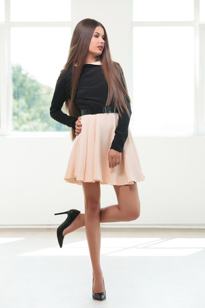 full length picture of a young fashion woman posing on one leg while holding a hand on her hip and looking to the side, away from the camera photo