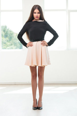 hands on hips: full length photo of a young fashion woman standing with her hands on her hips in a studio with natural light and looking into the camera