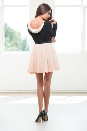 back view of a young fashion woman looking to her side while touching her shoulder with her hand photo