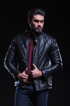 frowned: bearded casual young man looking away from the camera with a frowned face while holding his hands on his leather jacket. on a black background  Stock Photo
