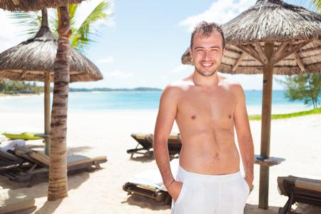 entspannte junge Mann mit den Händen in den Taschen am Strand mit Liegestühlen und Sonnenschirmen Stroh