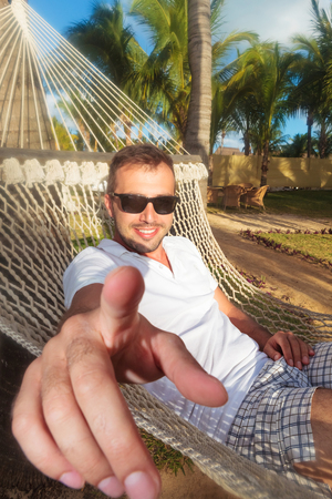 casual young man in a hammock in a resort pointing his finger to the camera photo