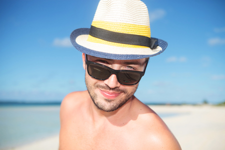 adorable face of a sexy young man on the beach with hat and sunglasses on photo