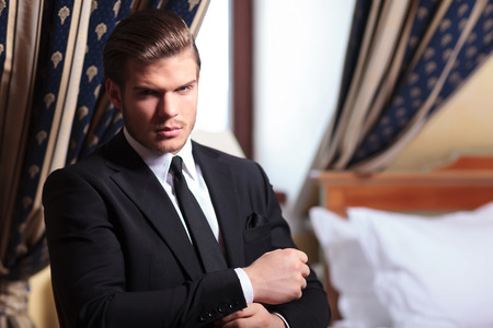 seated young business man fixing his cuffs while looking into the camera, in a vintage hotel room Stock Photo - 26328945