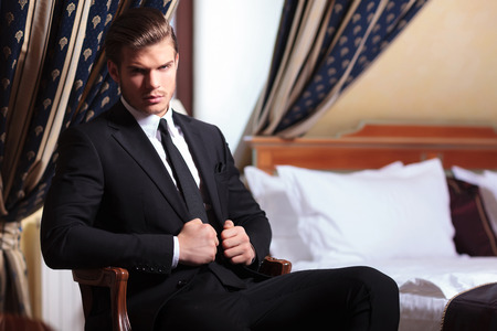 young business man sitting on a chair in a vintage hotel room and looking into the camera while holding his hands on his suit jacket photo