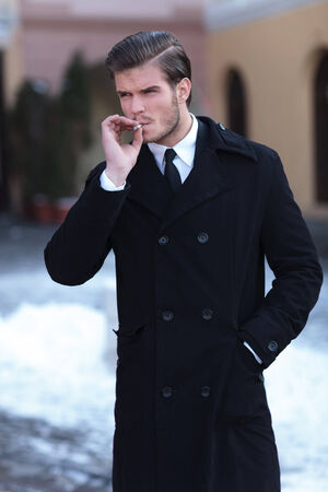 young business man smoking outdoor while holding a hand in his overcoat pocket and looking away from the camera photo