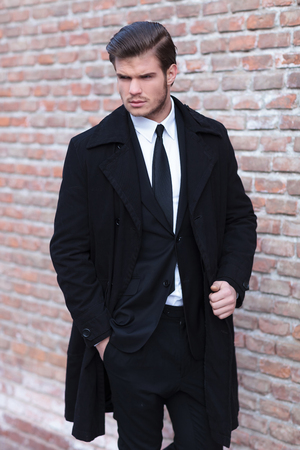 young business man posing outdoor with a hand in his pocket and the other on his overcoat while looking to his side, away from the camera Stock Photo