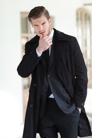 suit jacket: young business man posing outdoor touching his lower lip while looking into the camera and holding a hand in his pocket