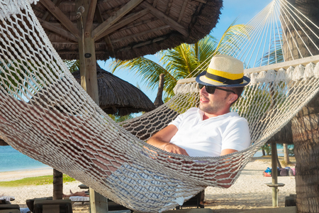 relaxed man in a hammock on the beach under straw umbrellas