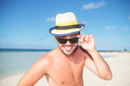 happy young man on the beach taking off his glasses and smiles photo