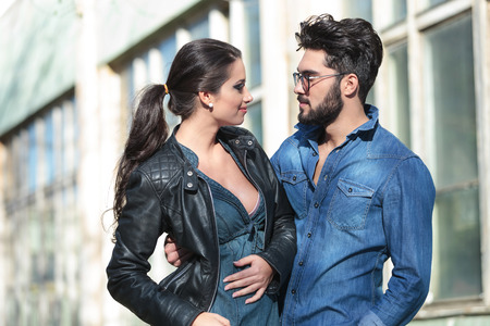 two sexy women: young casual couple looking at each other and smiling while he is embracing her