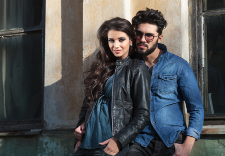 sexy love: young casual couple standing with hands in pockets near an old building and looking into the camera Stock Photo