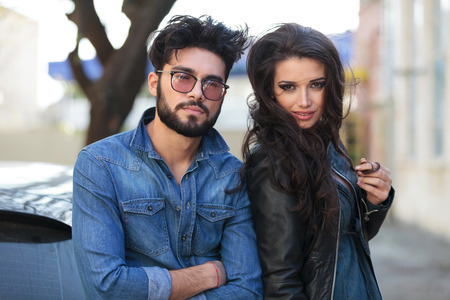 outdoor closeup portrait of a young casual couple looking into the camera. the man is holding his arms folded while the woman is curling her hair on her finger photo