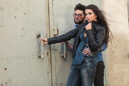 joven pareja ocasional abrazada en el viento y mirando a la c�mara mientras sostiene una vieja puerta met�lica photo
