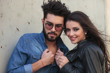 two sexy women: young casual couple holding their jackets while the man is looking down, away from the camera and the woman is looking at you